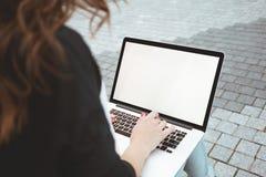 Il punto di vista posteriore della donna di affari è lavoro sulla tastiera del computer portatile sopra all'aperto a urbano Fotografia Stock