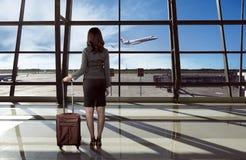 Il punto di vista posteriore della donna asiatica porta la valigia nell'aeroporto Immagini Stock Libere da Diritti