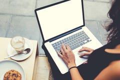 Il punto di vista posteriore della donna di affari sta scrivendo il testo a macchina sulla tastiera del computer portatile durant Fotografia Stock Libera da Diritti
