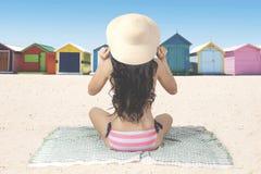 Il punto di vista posteriore della donna si siede sulla spiaggia fotografia stock libera da diritti
