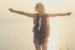 Il punto di vista posteriore della ragazza di viaggiatore con zaino e sacco a pelo sta stando sulla roccia immagine stock libera da diritti