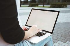 Il punto di vista posteriore della studentessa è lavoro sulla tastiera del computer portatile sopra all'aperto a urbano Fotografia Stock Libera da Diritti