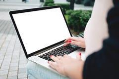 Il punto di vista posteriore della studentessa è lavoro sulla tastiera del computer portatile sopra all'aperto a urbano Fotografia Stock