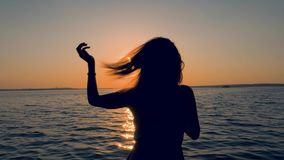 Il punto di vista posteriore delle donne sulla costa corregge i suoi capelli nei raggi del tramonto video d archivio