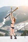 Il punto di vista posteriore dello sciatore felice della donna in costume da bagno che sta sul pendio e che tiene scia testa di c fotografia stock