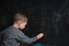 Il punto di vista posteriore dello studente maschio della scuola elementare scrive sulla lavagna Fotografia Stock Libera da Diritti