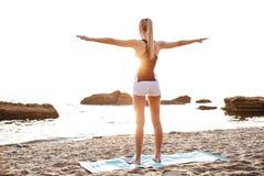Il punto di vista posteriore di bella giovane donna che fa l'allungamento si esercita Fotografia Stock Libera da Diritti