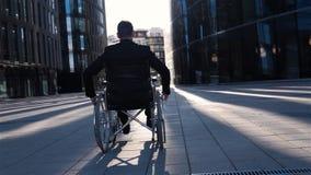 Il punto di vista posteriore di un uomo d'affari invalido in sedia a rotelle si muove nel distretto aziendale video d archivio