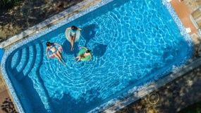 Il punto di vista superiore aereo della famiglia nella piscina da sopra, in madre ed in bambini felici nuota sulle guarnizioni di Immagini Stock Libere da Diritti