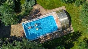 Il punto di vista superiore aereo della famiglia nella piscina da sopra, in madre ed in bambini nuota sulle guarnizioni di gomma  Fotografie Stock