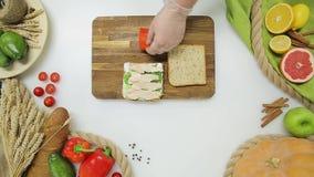 Il punto di vista superiore del capo passa le verdure e la carne di taglio, cucinanti un panino Stile di vita sano, alimento di d stock footage