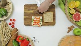 Il punto di vista superiore del capo passa le verdure e la carne di taglio, cucinanti un panino Stile di vita sano, alimento di d archivi video