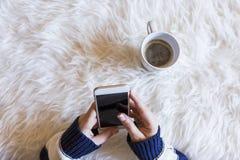 Il punto di vista superiore della donna passa la tenuta dello Smart Phone sopra fondo bianco Tazza di caffè inoltre lifestyles al immagini stock libere da diritti