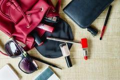 Il punto di vista superiore delle donne insacca gli accessori cosmetici femminili della roba Fotografie Stock Libere da Diritti