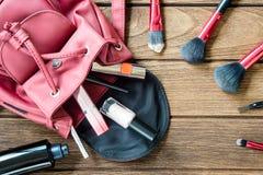 Il punto di vista superiore delle donne insacca gli accessori cosmetici femminili della roba su woode Fotografie Stock Libere da Diritti