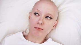 Il punto di vista superiore di una donna del malato di cancro che si trova nel letto, sveglia ed è spaventato ed interessato archivi video