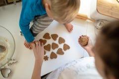Il punto di vista superiore di una madre e del suo bambino del bambino che fanno il cuore ha modellato i biscotti immagini stock libere da diritti