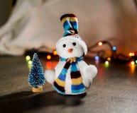 Il pupazzo di neve bianco di Natale sveglio in un cappello ed in poco albero del giocattolo nei precedenti si accende Fotografia Stock Libera da Diritti