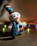 Il pupazzo di neve bianco di Natale sveglio in un cappello ed in poco albero del giocattolo nei precedenti si accende Immagine Stock