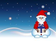 Il pupazzo di neve che porta un regalo e che porta un costume di Santa Claus con il fondo della stella, del cielo e della collina Fotografie Stock