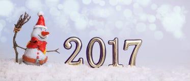 Il pupazzo di neve di Natale nella neve è nuovo nel 2017 contro il contesto di Immagini Stock Libere da Diritti