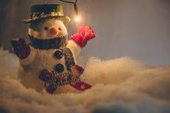 Il pupazzo di neve e la neve sta cadendo, supporto fra il mucchio di neve alla notte silenziosa con una lampadina Fotografie Stock Libere da Diritti