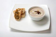 Il purè della minestra si espande rapidamente in un piatto bianco profondo Fotografie Stock