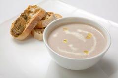 Il purè della minestra si espande rapidamente in un piatto bianco profondo Fotografia Stock