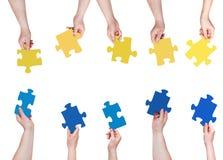 Il puzzle blu e giallo collega in mani della gente Immagine Stock