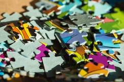Il puzzle dei bambini sparsi su una tavola di legno Immagini Stock
