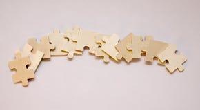 Il puzzle di legno è presentato in una fila Fotografia Stock Libera da Diritti