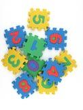 Il puzzle di numeri ha sparso su priorità bassa bianca Immagini Stock Libere da Diritti