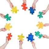 Il puzzle dipinto collega in mani della gente nel cerchio Fotografia Stock