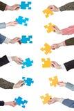 Il puzzle giallo e blu collega in mani della gente Immagine Stock