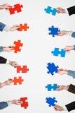 Il puzzle rosso e blu collega in mani della gente Fotografie Stock Libere da Diritti