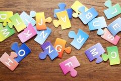 Il puzzle variopinto segna il fondo con lettere Fotografie Stock Libere da Diritti