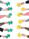 Il puzzle verde e giallo collega in mani della gente Fotografia Stock