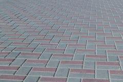 Il quadrato o su un marciapiede ha allineato con le mattonelle marroni e grige, pietre per lastricati fotografia stock