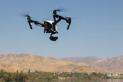 Il quadrocopter nero sta volando su nel cielo Immagine Stock