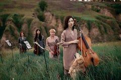 Il quartetto musicale femminile con i violini ed il violoncello prepara giocare al prato di fioritura Fotografie Stock Libere da Diritti