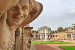Il raccolto sorridente della statua del satiro nudo del primo piano con la fontana ed il giardino Fotografie Stock Libere da Diritti