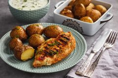 Il raccordo arrostito del pollo con le patate al forno ed il yogurt dell'aglio immerge fotografia stock