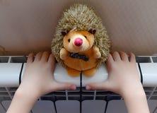 Il radiatore del riscaldamento riscalda le mani del bambino Immagini Stock Libere da Diritti