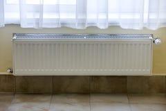 Il radiatore di riscaldamento con la valvola del termostato sulle mattonelle leggere della parete copia il fondo dello spazio Int immagine stock