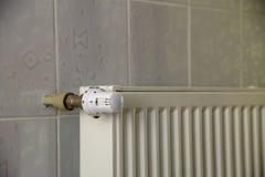 Il radiatore di riscaldamento con la valvola del termostato sulle mattonelle leggere della parete copia il fondo dello spazio Int fotografie stock libere da diritti