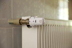 Il radiatore di riscaldamento con la valvola del termostato sulle mattonelle leggere della parete copia il fondo dello spazio Int fotografia stock