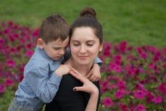 Il ragazzino abbraccia una madre sorridente Immagini Stock