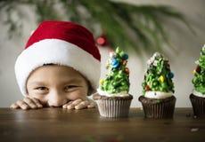 Il ragazzino allegro con l'albero di Natale ha decorato i bigné Immagini Stock Libere da Diritti