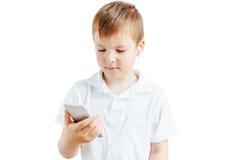 Il ragazzino ascolta musica e parla sul telefono con fondo bianco Fotografia Stock Libera da Diritti