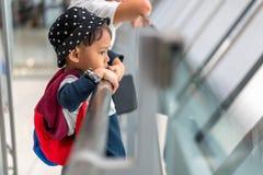 Il ragazzino asiatico 3 anni porta l'imbarco aspettante della borsa al volo nel corridoio terminale di transito dell'aeroporto de fotografia stock libera da diritti